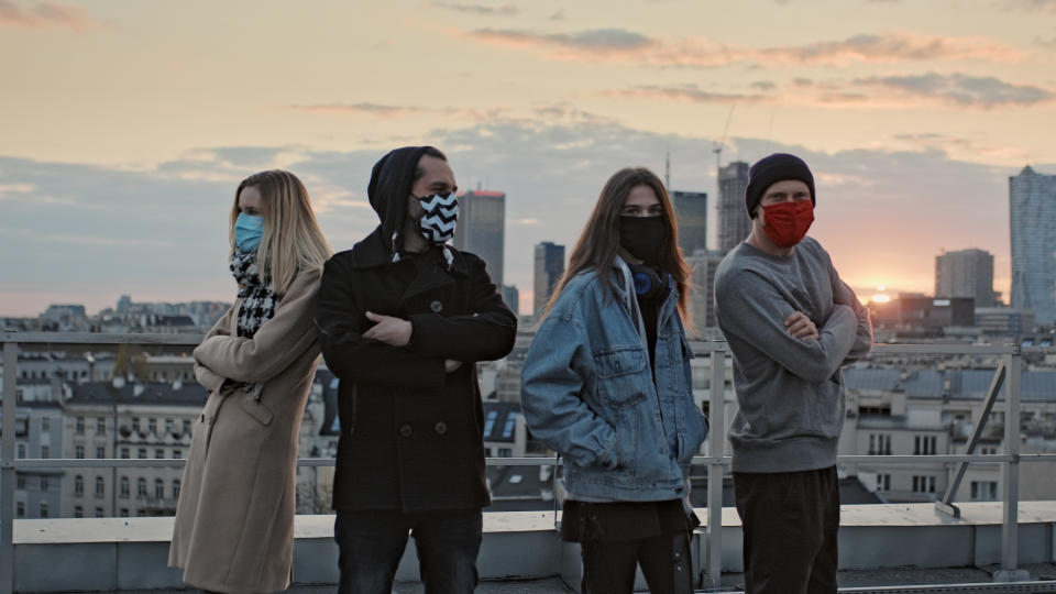 Young people meeting on a rooftop. Wearing masks and keeping distance