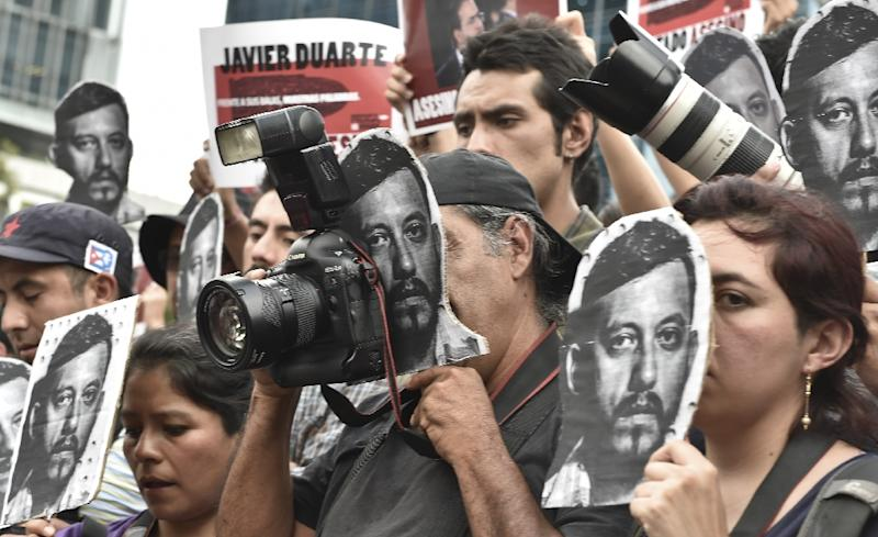 Mexican photojournalists hold pictures of their murdered colleague Ruben Espinosa during a demonstration held at the Angel of Independence square in Mexico City, on August 2, 2015 (AFP Photo/Yuri Cortez)