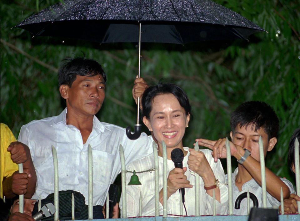 In this July 16, 1995, file photo, an unidentified aid holds up an umbrella over Burmese democratic leader Aung San Suu Kyi during her daily appearance at the gate of her Yangon (formerly known as Rangoon) home from where she greets a crowd of supporters that gathered in the street. After Myanmar's military staged a coup Monday, Feb. 1, 2021, Aung San Suu Kyi finds herself back under house arrest. But this time, her standoff with the generals comes after she has sorely disappointed many once-staunch supporters in the international community. (AP Photo/Anat Givon, File)
