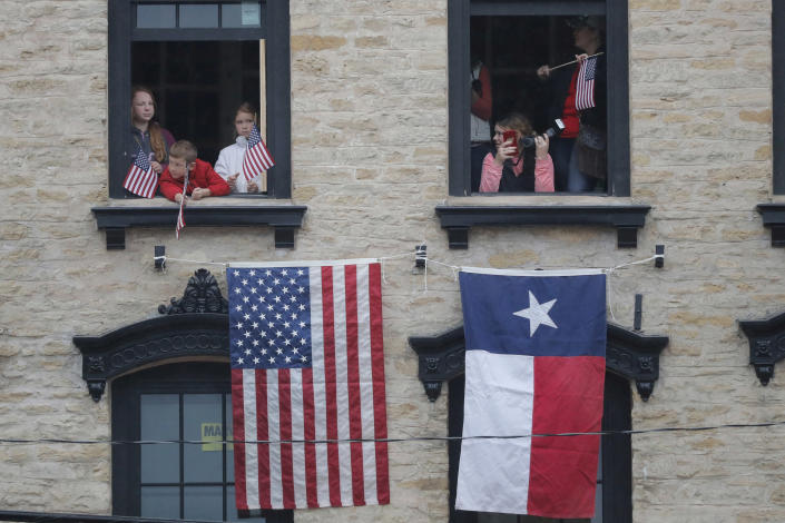 People look from a building as they pay their respects as the train carrying the casket of former President George H.W. Bush passes through Navasota, Texas Thursday, Dec. 6, 2018. (Photo: Gerald Herbert/AP)