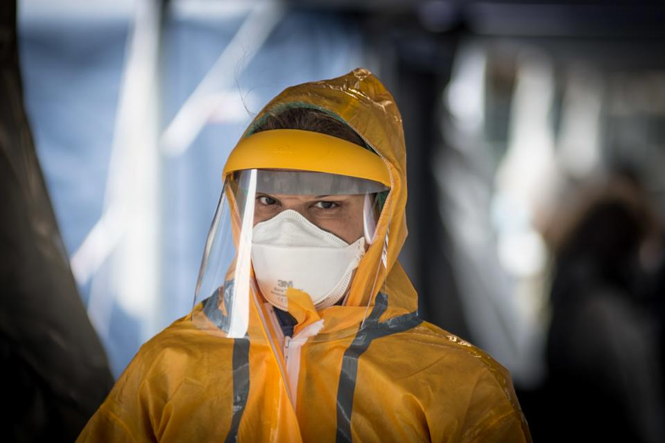 The hospital worker wearing a mask and protective equipment in a tent set up for the triage of patients, at a temporary emergency facility set up outside the accident and emergency department, where any new arrivals who present suspected new symptoms of coronavirus, at the hospital in Northern Italy. Source: Getty Images