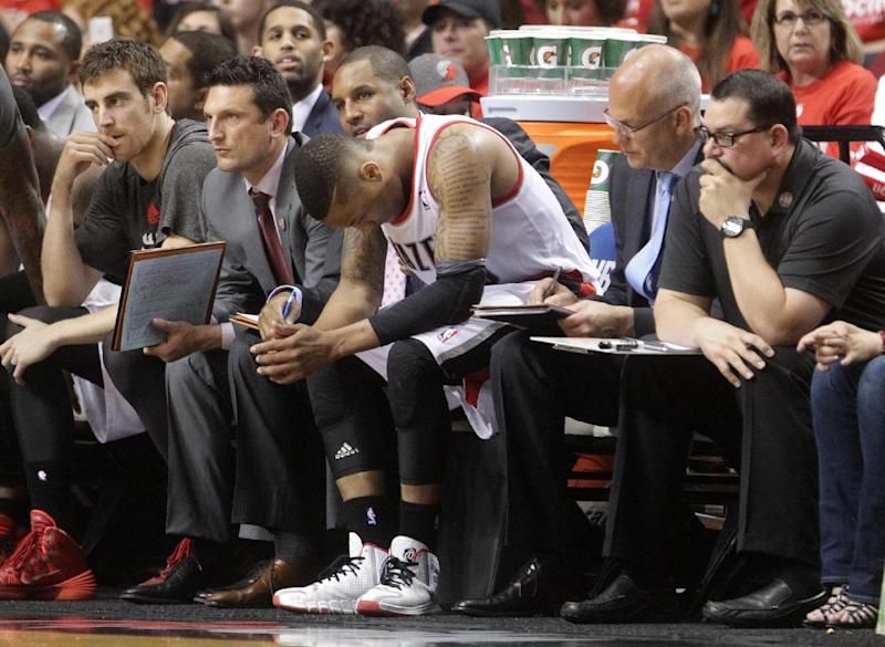Portland Trail Blazers' Damian Lillard, center, sits on the bench near the end of Game 3 of a Western Conference semifinal NBA basketball playoff series against the San Antonio Spurs, Saturday, May 10, 2014, in Portland, Ore. The Spurs won 118-103. (AP Photo/Rick Bowmer)