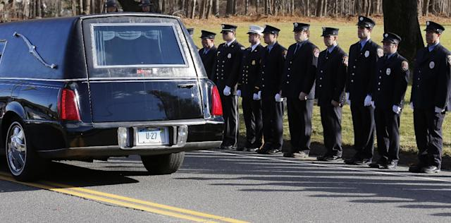 Firefighters stand as the procession heads to the cemetery outside the funeral for school shooting victim Daniel Gerard Barden at St. Rose of Lima Catholic Church in Newtown, Conn., Wednesday, Dec. 19, 2012. According to firefighters, Daniel wanted to be a firefighter when he grew up and they honored him at the service. Barden, 7, was killed when Adam Lanza walked into Sandy Hook Elementary School in Newtown, Conn., Dec. 14, and opened fire, killing 26 people, including 20 children, before killing himself. (AP Photo/Charles Krupa)