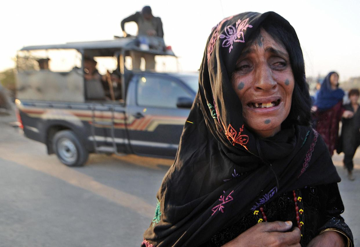 An Afghan refugee woman cries after troops arrest her relative during a search operation in the Afghan refugee camp in Karachi on December 2, 2008.