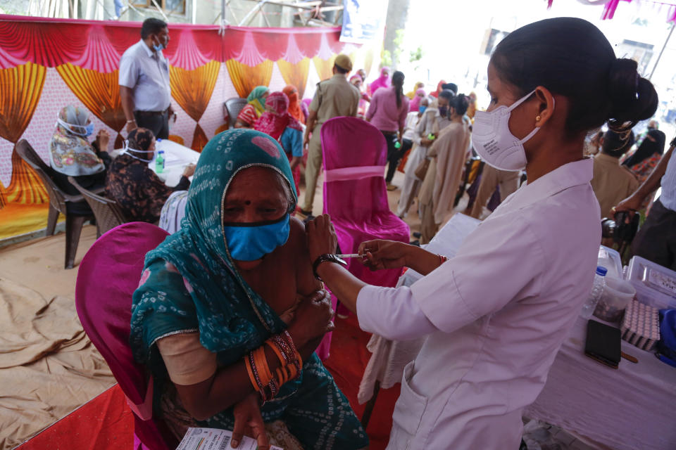 A woman is administered the Covishield vaccine during a vaccination drive against COVID-19 at a mosque in Ahmedabad, India, Monday, June 21, 2021. Every adult in India will now be eligible for a free vaccine paid for by the federal government as a new policy shift kicks in Monday, while coronavirus cases in the country continue to plummet. (AP Photo/Ajit Solanki)