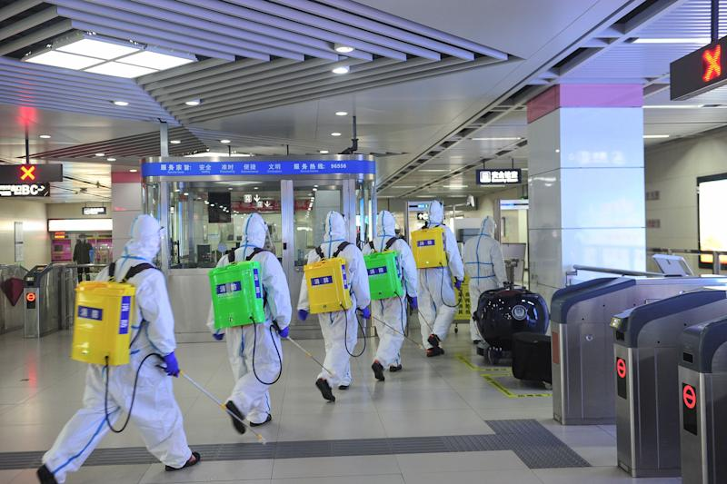 Staff members spray disinfectant at a subway station in Wuhan, in China's central Hubei province, as the subway prepares to reopen to the public after closing due to the COVID-19 coronavirus outbreak. - China reported more than 50 imported cases of the coronavirus on March 27, hours after announcing a ban on foreigners entering the country. (Photo by STR / AFP) / China OUT (Photo by STR/AFP via Getty Images)