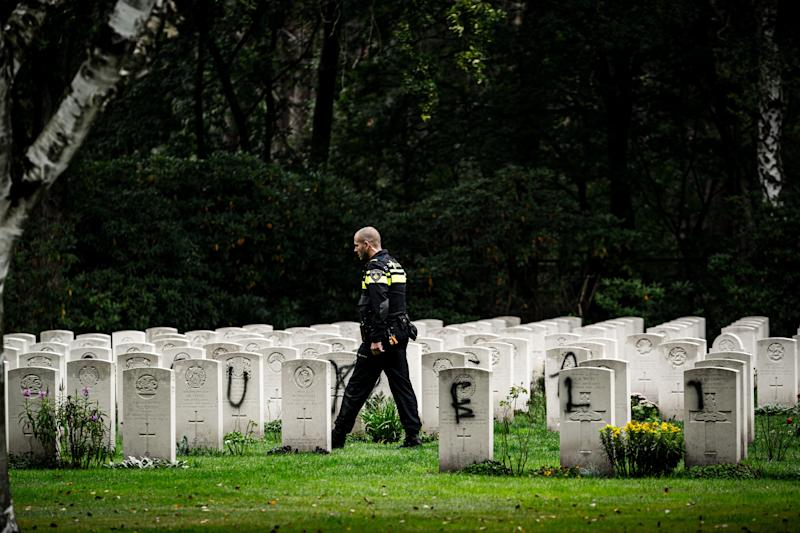 A police officer walks past graves which have been vandalised with graffiti, and a large swastika was daubed on the inner wall of the chapel in the British World War II Commonwealth Graves cemetery in Mierlo, east of Eindhoven, Netherlands, on September 13, 2019. (Photo by Rob Engelaar / ANP / AFP) / Netherlands OUT (Photo credit should read ROB ENGELAAR/AFP/Getty Images)