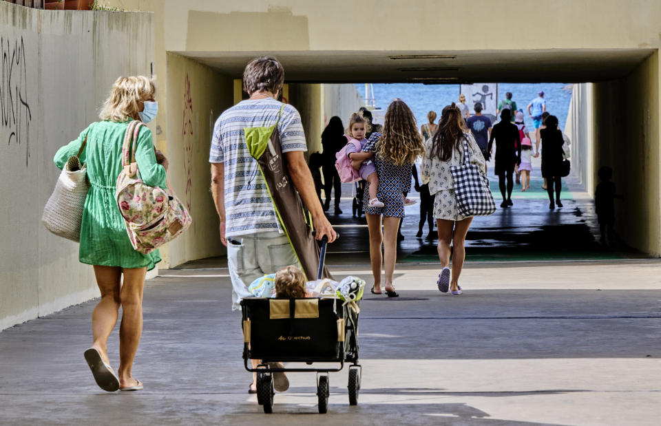 ESTORIL, PORTUGAL - JULY 10: Mask-clad beachgoers cart their baby as they arrive in Praia das Poças on a warm and sunny morning during the COVID-19 Coronavirus pandemic on July 10, 2021, in Estoril, Portugal. Sixty of the 278 municipalities in mainland Portugal are, as of today, at high or very high risk of COVID-19 incidence, 15 more than last week, and being subject to more restrictive measures, including curfews at night. The Council of Ministers decided last July 08 new measures to contain the pandemic at a time when the Portuguese vacations period intensifies. Locals and tourists have to present a negative test or digital certificate to access tourist establishments and local accommodation in continental Portugal, and they will have to do the same to be in the interior of restaurants on Fridays from 19.00 hours and throughout the day on Saturdays, Sundays and holidays in municipalities with high and very high risk. Non compliance of the regulations by those at restaurants and hotels are liable to be fined between 100 and 500 euros and establishment owners will be subjected to fines between 1,000 and 10,000 euros. (Photo by Horacio Villalobos#Corbis/Corbis via Getty Images)