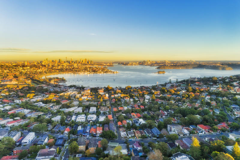 Wealthy Eastern suburbs of Sydney city around Harbour in aerial view with soft morning light and blue sky.