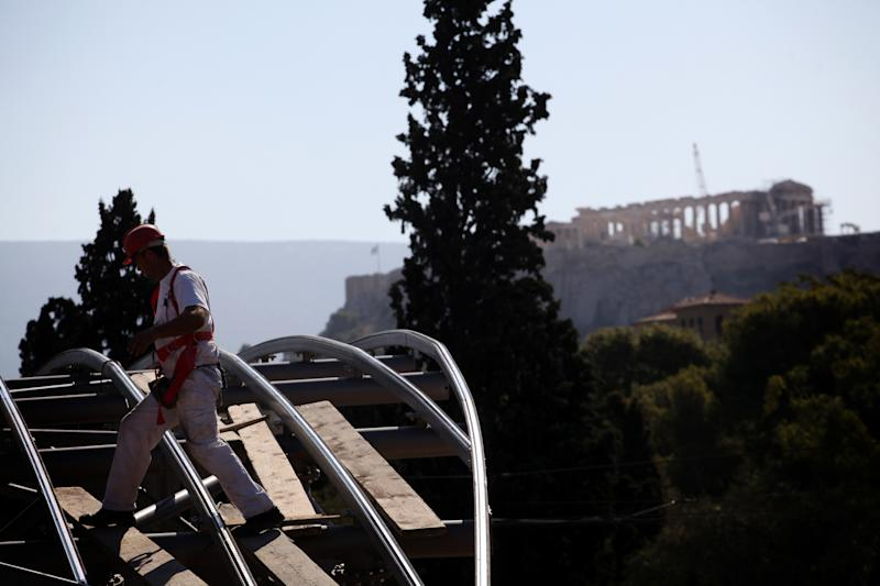 A worker walks on the roof top of a construction site for a new car parking area of a metro station as the ancient Parthenon temple is seen in the background, on Wednesday, Oct. 3, 2012. According to forecasts in the draft budget submitted to Greece's Parliament on Monday this year's recession will see the economy shrink around 6.5 percent, the document estimated. Unemployment is predicted to rise to 24.7 percent in 2013 from an average 23.5 percent in 2012.(AP Photo/Petros Giannakouris)