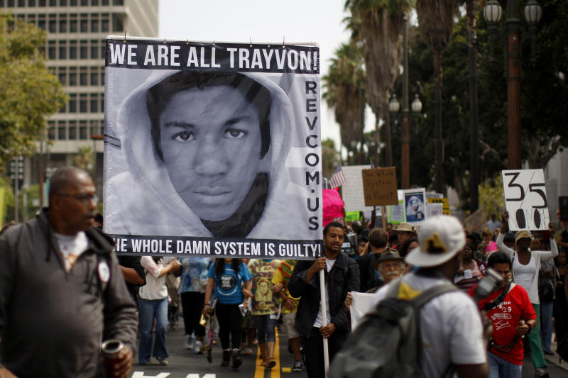 <strong>People carry a photo of Trayvon Martin during a march to protest the verdict in the George Zimmerman trial, after he was acquitted of shooting Martin dead. Young black men are far more likely to be killed by gunfire than white men</strong> (David McNew / Reuters)