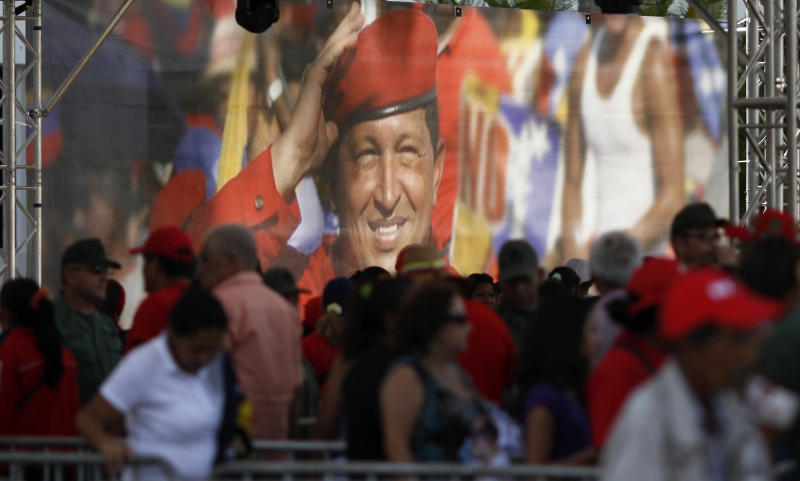 A large image of Venezuela's late President Hugo Chavez is on display where mourners line up to view his body lying in state at the military academy in Caracas, Thursday, March 7, 2013. While Venezuela remains deeply divided over the country's future, the multitudes weeping and crossing themselves as they reached the president's coffin early Thursday were united in grief and admiration for a man many considered a father figure. (AP Photo/Ariana Cubillos)