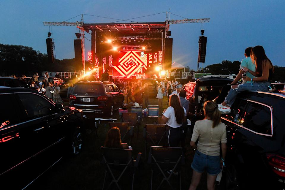 """<div class=""""caption""""> The """"Safe & Sound"""" Drive-In Concert in Water Mill, New York, July 25, 2020. </div> <cite class=""""credit"""">Kevin Mazur / Getty Images</cite>"""