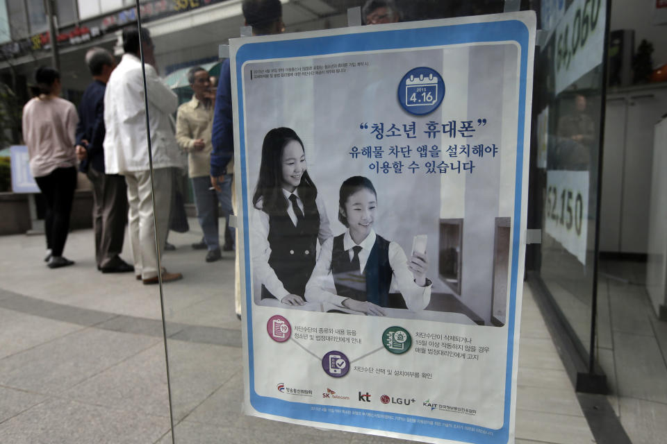 Image: A promotional banner of mobile apps that block harmful content, is posted on the door at a mobile store in Seoul, South Korea. (Lee Jin-man / AP file)