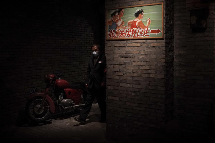 A man wearing a face mask to help curb the spread of the coronavirus walks through an old Beijing's hutong alley inside a shopping mall in Beijing, Monday, Jan. 18, 2021. A Chinese province grappling with a spike in coronavirus cases is reinstating tight restrictions on weddings, funerals and other family gatherings, threatening violators with criminal charges. (AP Photo/Andy Wong)