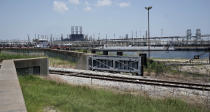 """A flood gate and seawall that will be increased is shown near a refinery Thursday, July 26, 2018, in Port Arthur, Texas. The oil industry wants the government to help protect some of its facilities on the Texas Gulf Coast against the effects of global warming. One proposal involves building a nearly 60-mile """"spine"""" of flood barriers to shield refineries and chemical plants. Many Republicans argue that such projects should be a national priority. But others question whether taxpayers should have to protect refineries in a state where top politicians still dispute whether climate change is real. (AP Photo/David J. Phillip)"""