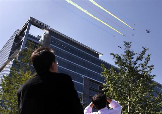 Office workers look up at Chinese Air Force fighter jets as they fly over a building near Beijing's Tiananmen Square September 21, 2009, during a rehearsal for the National Day parade.
