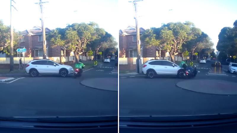 A delivery driver on a scooter in green enters the roundabout from the left and both vehicles collide resulting in the delivery driver being knocked off the scooter.