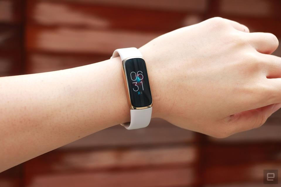 <p>Front view of the Fitbit Luxe with a light pink silicone band on a wrist against a dark brown paneled background. The screen shows the time is 6:31pm.</p>
