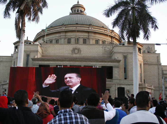 FILE -- In this Saturday, Nov. 17, 2012 file photo Egyptians watch Turkish Prime Minister Recep Tayyip Erdogan on a screen outside the Cairo University building where he made an address to a packed hall in Cairo, Egypt. Egyptians are closely following protests in Turkey, a country that has provided the heavily polarized and increasingly impoverished Egyptians with a tantalizing model for marrying Islamist government with a secular establishment and achieving prosperity along the way. With muted reservations on his secularism talk, Erdogan's Egyptian admirers in the Muslim Brotherhood gave him a hero's welcome when he visited Egypt last year, erecting giant billboards carrying his image on Cairo's main bridges and boulevards. (AP Photo/Ahmed Abd el Fattah, File)