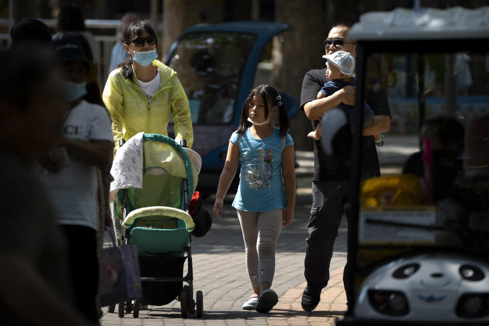 Adults and children walk along a path at a public park in Beijing, Saturday, Aug. 21, 2021. China will now allow couples to have a third child as the country seeks to hold off a demographic crisis that threatens its hopes of increased prosperity and global influence. (AP Photo/Mark Schiefelbein)