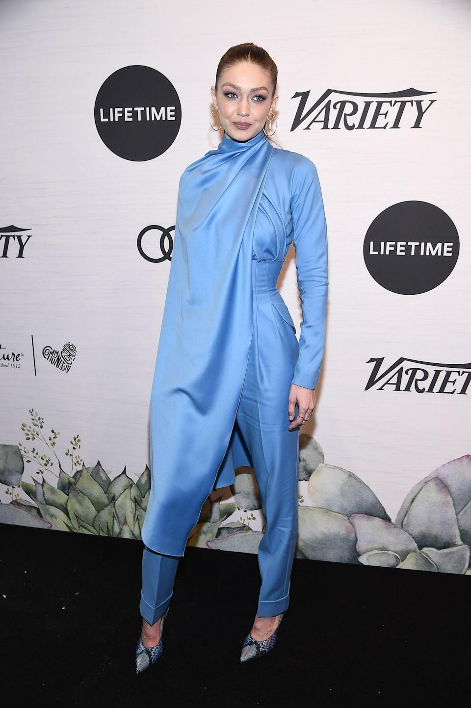 While not all heroes wear capes, we sure do appreciate it when they do — <em>especially</em> when they look as good as Gigi does in this powder-blue asymmetrical caped jumpsuit by British designer Emilia Wickstead. Avengers, take notes!