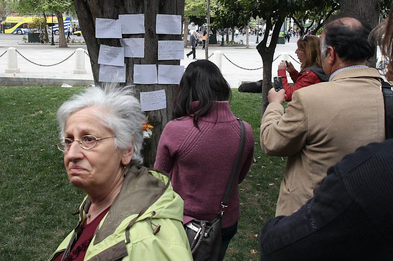 People gather at the site where an elderly man fatally shot himself at Athens' main Syntagma square on Wednesday, April 4, 2012. The Greek pensioner picked the busiest public area in Athens to shoot himself dead on Wednesday, leaving a note which police said linked his suicide with the country's acute financial woes. (AP Photo/Thanassis Stavrakis)