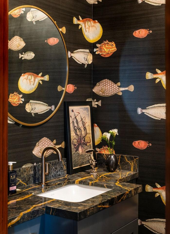 Fornasetti's Acquario wallpaper for Cole and Son brings an aquatic theme to the powder room.