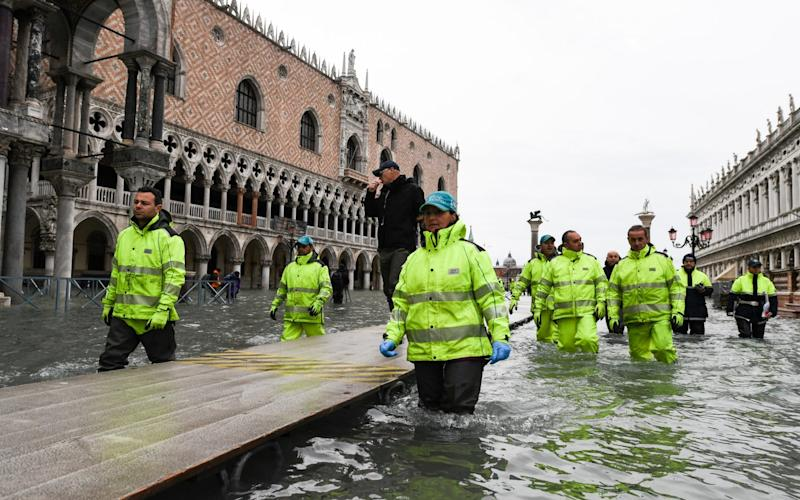 Visitors walk in flooded Venice, in the morning of November 17, 2019 during