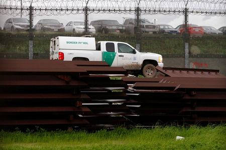 A U.S. border patrol vehicle drives past metal sections to be used to fix the border fence between  Mexico and the U.S., as seen from Tijuana, Mexico, February 14, 2019. REUTERS/Jorge Duenes