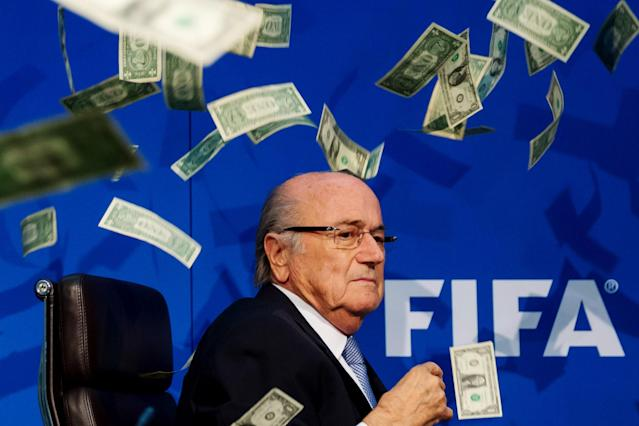 Sepp Blatter was showered in dollar bills during a news conference. (Getty)