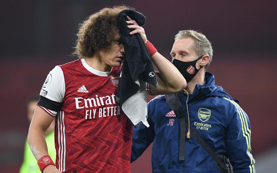 David Luiz of Arsenal receives treatment from Physio Jordan Reece for a head injury during the Premier League match between Arsenal and Wolverhampton Wanderers at Emirates Stadium on November 29, 2020 in London, England. Sporting stadiums around the UK remain under strict restrictions due to the Coronavirus Pandemic as Government social distancing laws prohibit fans inside venues resulting in games being played behind closed doors - Arsenal FC/David Price