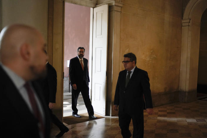 Brazil's Foreign Minister Ernesto Araujo, in doorway, arrives for a press conference after a BRICS meeting in Rio de Janeiro, Brazil, Friday, July 26, 2019. BRICS is a grouping of major emerging economies encompassing Brazil, Russia, India, China and South Africa. The delegations from the BRICS nations begin meeting Friday to pave the way for a summit in November. (AP Photo/Leo Correa)