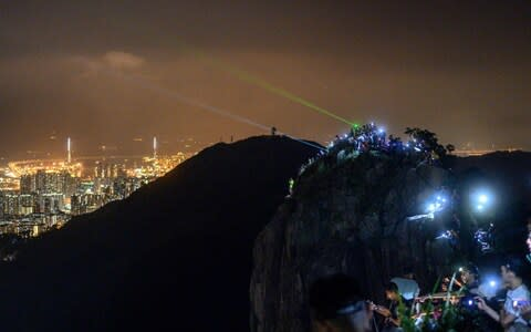 People light up laser beams at the hill top of Lion Rock in Hong Kong  - Credit: AFP
