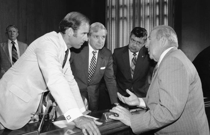 FILE - In this July 13, 1982, file photo Secretary of State designate George Shultz, right, speaks with members of the Senate Foreign Relations Committee prior to the start of the afternoon session of the panel on Capitol Hill in Washington. From left are, Sen. Joseph Biden, D-Del.; Sen. Charles Percy, R-Ill., chairman of the panel and Sen. Edward Zorinsky, D-Neb. Shultz, former President Ronald Reagan's longtime secretary of state, who spent most of the 1980s trying to improve relations with the Soviet Union and forging a course for peace in the Middle East, died Saturday, Feb. 6, 2021. He was 100. (AP Photo/Ira Schwarz, File)