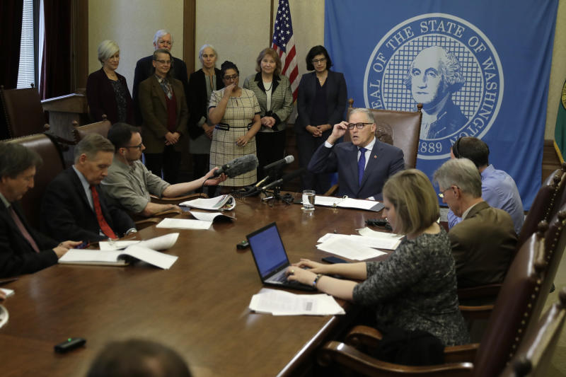 Washington Gov. Jay Inslee, seated center, talks to reporters about his proposed supplemental state budget, Wednesday, Dec. 18, 2019, at the Capitol in Olympia, Wash. (AP Photo/Ted S. Warren)