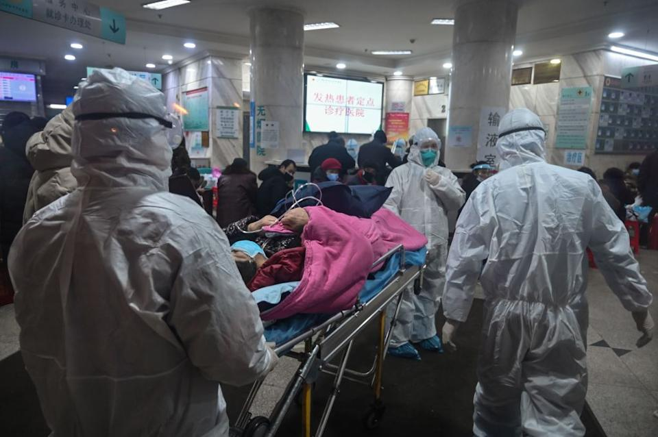 Medical staff wearing protective clothing arrive with a patient at the Wuhan Red Cross Hospital.