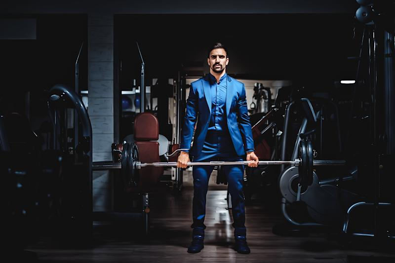 man wearing business suit lifting weight in a gym