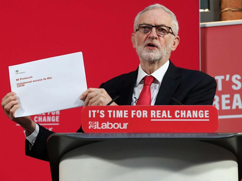 Corbyn shows a document during a news conference in London yesterday: Reuters