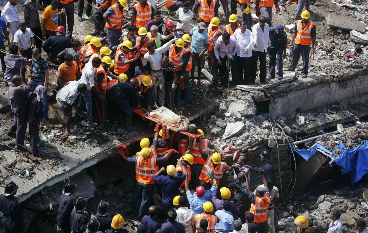 Rescue workers use a stretcher to carry a woman who was rescued from the rubble at the site of a collapsed residential building in Mumbai September 27, 2013. One person was killed and six injured when the five-storey building came crashing down in south Mumbai on Friday morning, local media quoted officials as saying. REUTERS/Danish Siddiqui (INDIA - Tags: DISASTER TPX IMAGES OF THE DAY)