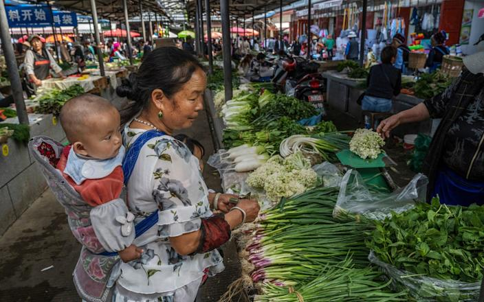 A Bai woman carries a baby on her back when purchasing goods at a local market on April 24, 2021 in Xizhou, Yunnan, China-Kevin Frayer & # xa0; / Getty Images AsiaPac & # xa0;