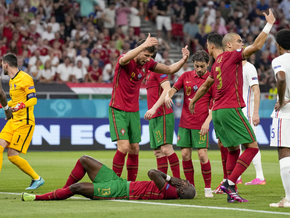 Portugal's Danilo Pereira lies on the pitch after a collision with France's goalkeeper Hugo Lloris, left, during the Euro 2020 soccer championship group F match between Portugal and France at the Puskas Arena, Budapest, Hungary, Wednesday, June 23, 2021. (AP Photo/Darko Bandic,Pool)
