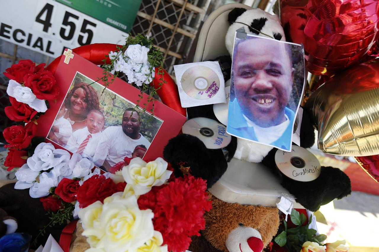 Photos of Alton Sterling are interspersed with flowers and mementos at a makeshift