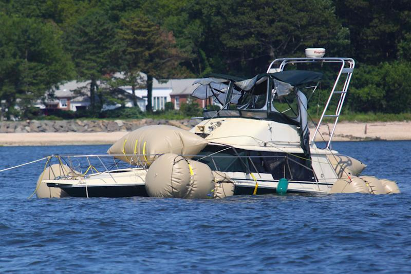 The Kandi Won is towed to shore after being raised from the bottom of Oyster Bay, off the shore of New York's long Island, Wednesday, July 11, 2012. The yacht capsized and sank, killing three children in its cabin, after a July Fourth outing to watch fireworks. Authorities were still trying to determine if the accident was caused by overcrowding or whether a mechanical malfunction, weather conditions or other factors could have been involved. (AP Photo/Howard Schnapp, Pool)