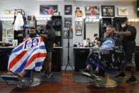FILE - In this July 15, 2020, file photo, Ricardo Rivera, left, has his hair cut by Anthony Acosta while Braunson McDonald has his hair cut by Luis Lopez, right, owner of Orange County Barbers Parlor in Huntington Beach, Calif. California Gov. Gavin Newsom this week ordered that indoor businesses like salons, barber shops, restaurants, movie theaters, museums and others close due to the spread of COVID-19. (AP Photo/Ashley Landis)