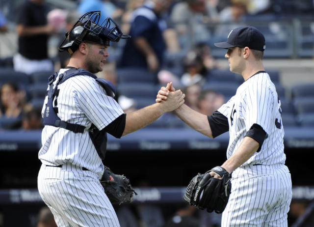 New York Yankees pitcher David Robertson, right, celebrates with catcher Brian McCann after the Yankees defeated the Chicago White Sox 5-3 in of a baseball game Saturday, Aug. 23, 2014, at Yankee Stadium in New York. (AP Photo/Bill Kostroun)