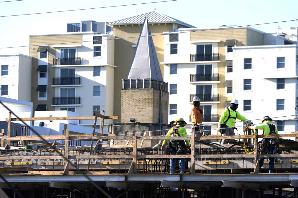 Construction workers build the new Overtown Youth Center, as the steeple from the historic St. John Baptist Church, and a recently built apartment building serve as a backdrop, Monday, May 24, 2021, in Miami. (AP Photo/Lynne Sladky)