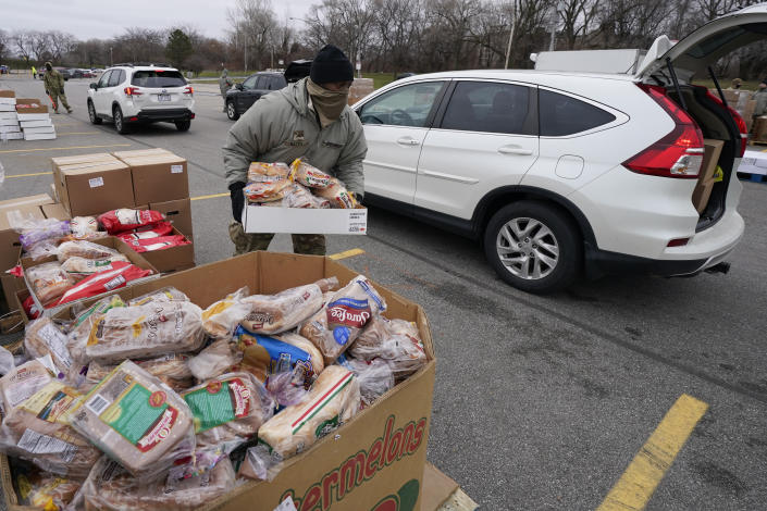 Corpl. James Bates carries a box of groceries to a car at a food bank distribution by the Greater Cleveland Food Bank, Thursday, Jan. 7, 2021, in Cleveland. (AP Photo/Tony Dejak)
