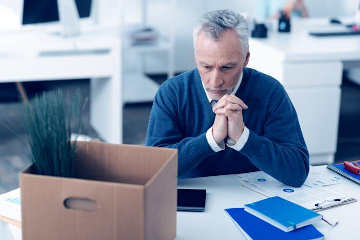 Nostalgic mood. Selective focus on a pensive mature employee thinking about something while sitting at his writing table and working with different printouts at work.�