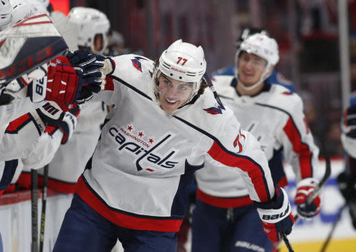 Washington Capitals right wing T.J. Oshie is congratulated as he passes the team box after scoring the go-ahead goal against the Colorado Avalanche during the third period of an NHL hockey game Thursday, Feb. 13, 2020, in Denver. The Capitals won 3-2. (AP Photo/David Zalubowski)